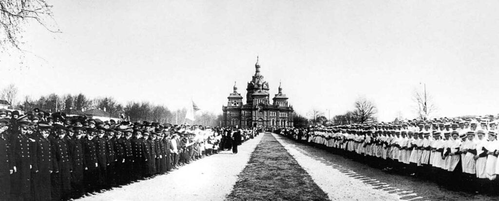 РГАКФД. Шифр: Ал-269а сн. 94. Учащиеся местных учебных заведений, выстроенные вдоль пути следования императора от станции к церкви, в ожидании императора. 3 мая (20 апреля) 1915 г.